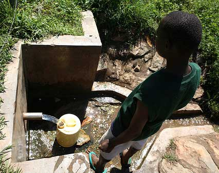 174b-A-Kenyan-boy-gathers-water-from-a-protected-spring-in-Busia