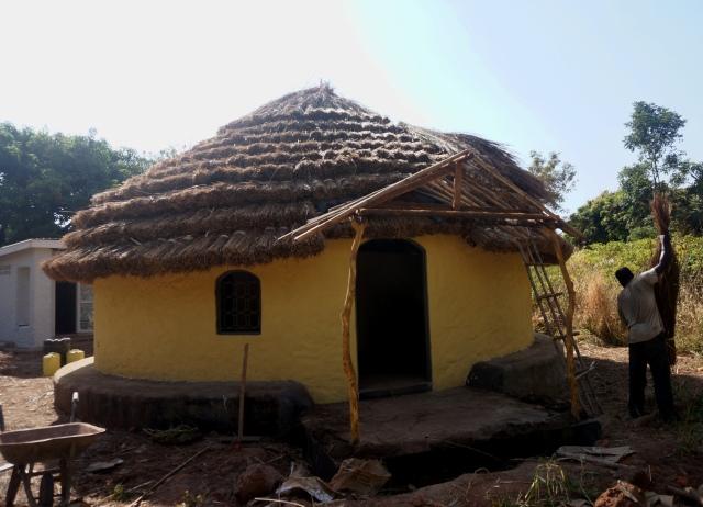 Kagwa outside hut